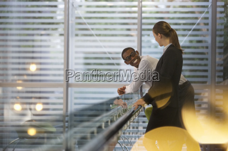 smiling businessman and businesswoman talking in
