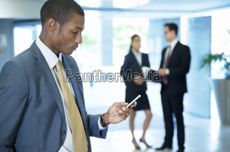 businessman text messaging with cell phone