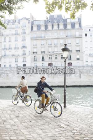 men riding bicycles along seine river