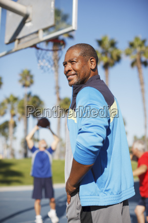 older man playing basketball on court