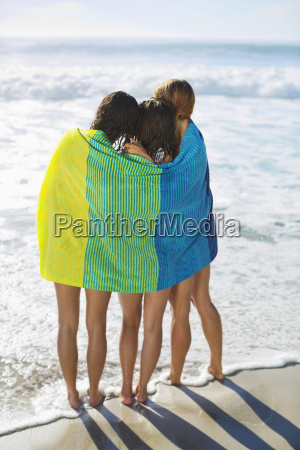 friends wrapped in towel on beach