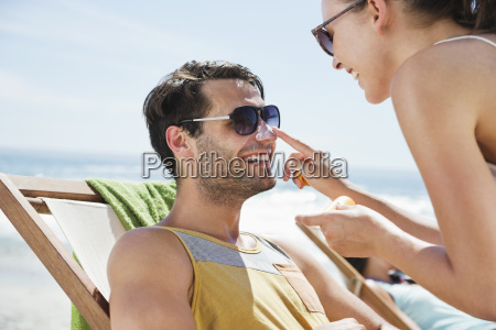 woman applying sunscreen to mans nose