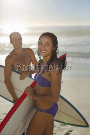 portrait of happy couple holding surfboards