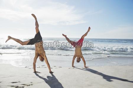 men in swim trunks doing handstands
