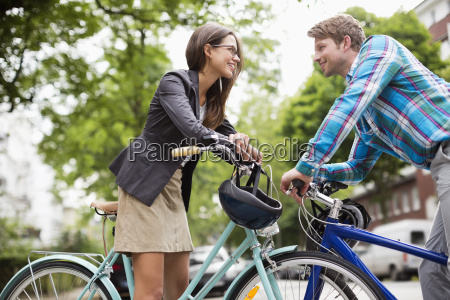 couple pushing bicycles on city street