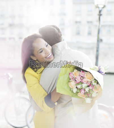 couple with bouquet of flowers hugging