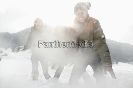 portrait of playful friends enjoying snowball