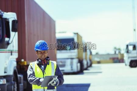 worker using digital tablet near trucks