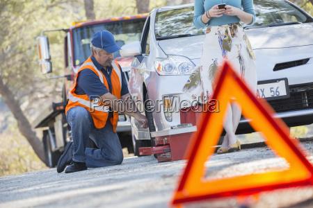 roadside mechanic changing tire behind warning