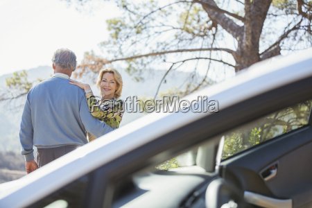 senior couple hugging at roadside outside
