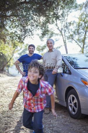 happy multi generation men outside car