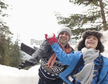 father and son enjoying snowball fight