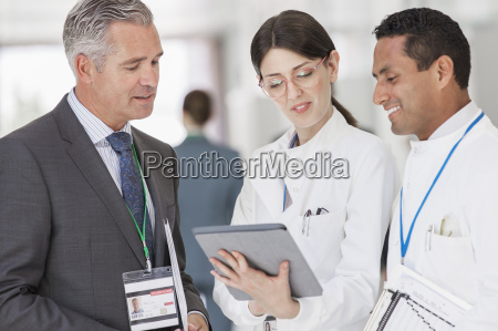 scientists and businessman reading digital tablet