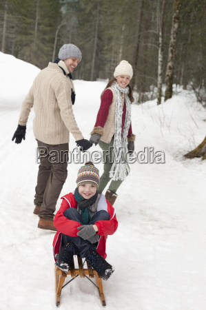 parents pulling happy boy on sled