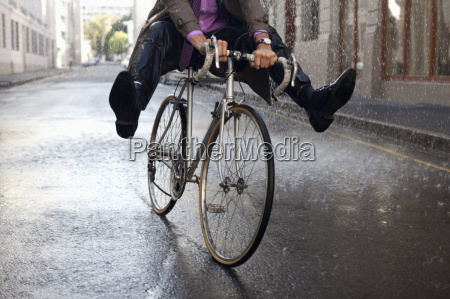 businessman riding bicycle with feet up