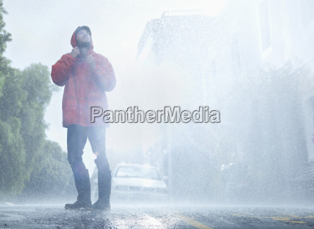 man wearing raincoat in rainy street
