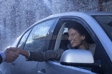 smiling businesswoman in car extending handshake
