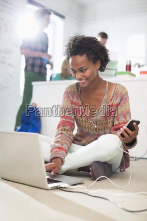 businesswoman using laptop on floor in