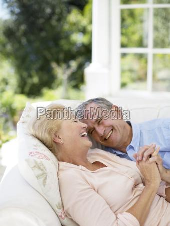 senior couple laying on patio sofa