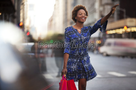 woman with shopping bags hailing taxi