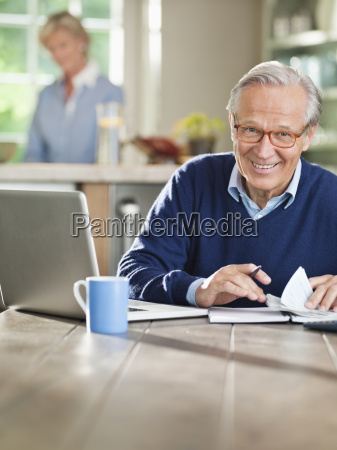 man using laptop at kitchen table