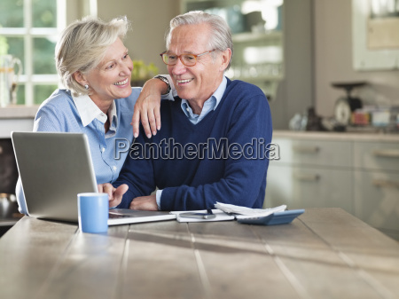 couple using laptop at kitchen table