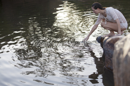 woman dipping hand into lake