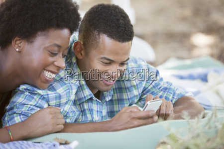 couple using cell phone on blanket