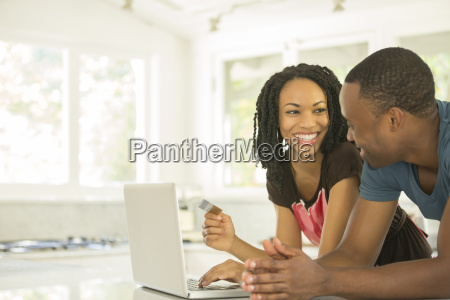 happy couple shopping online at laptop