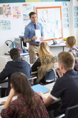 teacher talking to teenage students in