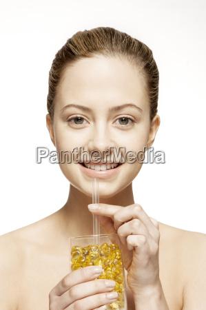 woman drinking glass of vitamins