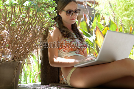 woman using laptop on patio