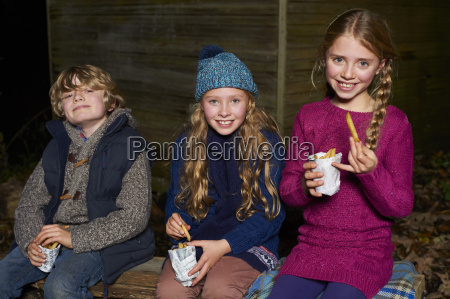 smiling children eating french fries at