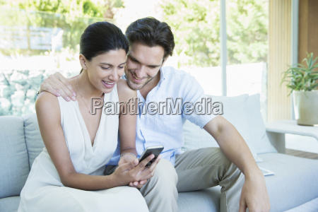 couple using cell phone on sofa