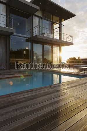 sun behind luxury house with swimming