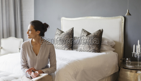 woman writing in bedroom
