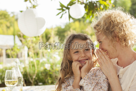 mother and daughter whispering outdoors