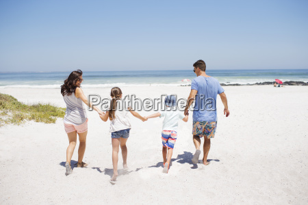 family holding hands and walking on