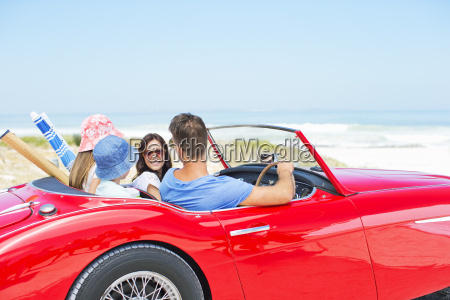 family driving convertible to beach