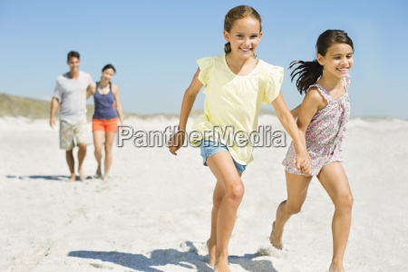 girls holding hands and running on