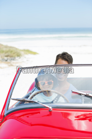 father and son driving convertible on