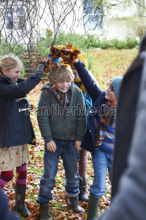 children playing in autumn leaves outdoors