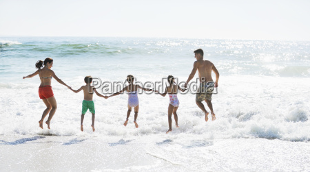 family jumping in surf on beach
