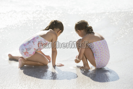 girls playing together in surf on