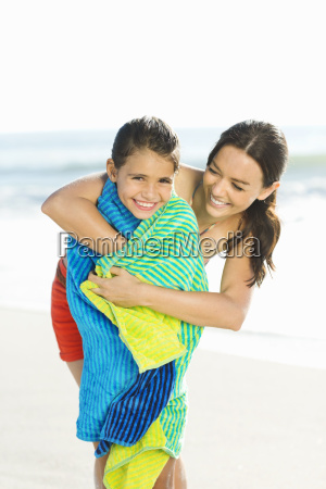 mother wrapping daughter in towel on