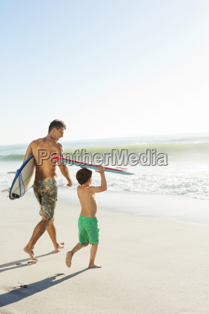 father and son carrying surfboard and