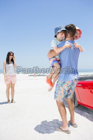 father hugging children on beach