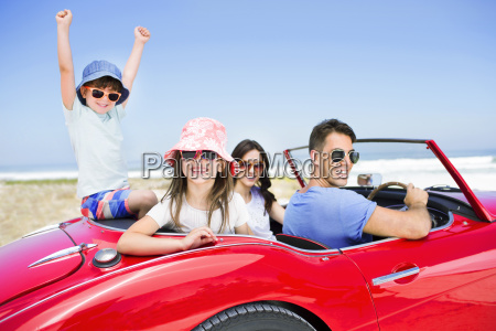 family in convertible at beach