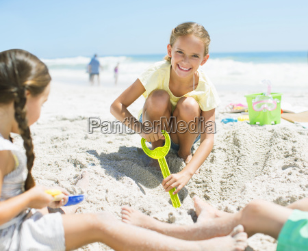 girls digging in sand on beach