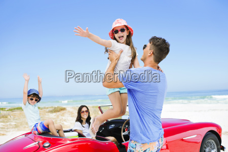 father lifting daughter from convertible at